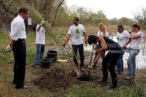Washington, DC - April 21, 2009 -- United States President Barack Obama observes as first lady Michelle Obama prepares the soil in a tree planting event at the Kenilworth Aquatic Gardens in Washington, DC, April 21, 2009. The event was organized by the Student Conservation Association, an Americorp organization. .Credit: Martin H. Simon - Pool via CNP