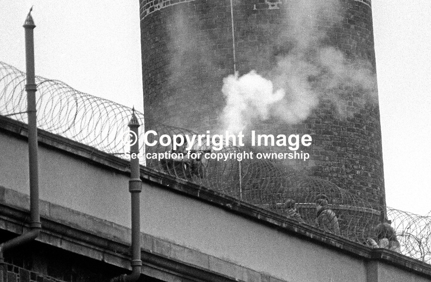 Soldier fires a baton round aka rubber bullet at Loyalist remand prisoners at Crumlin Road Jail, Belfast, N Ireland, who broke through the roof of their wing so that they could see Orangemen parade past the prison on their way to the main procession.  197307120504b<br />
