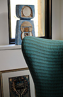 A detail of an Arne Jacobsen Egg chair upholstered in teal green is complemented by pieces of art displayed behind.