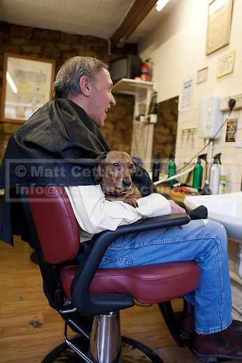 Adding to the community feel of the shop, a customer, Pete, complete with his disabled dog sits in the chair before his haircut.