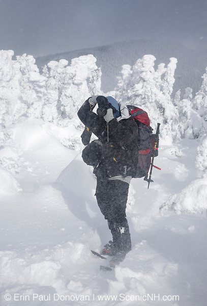 A hiker photographing along the Appalachian Trail (Carter-Moriah Trail) near the summit of Carter Dome in Bean's Purchase of the New Hampshire White Mountains during a windy winter day.
