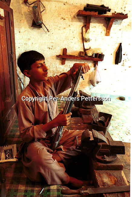 Sardar Masoom, age 16 is finishing the work on a shotgun copy he has made at a weapons factory on September 22, 2001 in Darra a village about 40 kilometers south of Peshawar, Pakistan. These factories have made copies of weapons for over one hundred years and they are sold to conflicts in Afghanistan, The Balkans and Kashmir and other conflict areas. These weapons are also smuggled into Afghanistan to the Taleban movement..Photo: Per-Anders Pettersson/ Grazia Neri.....