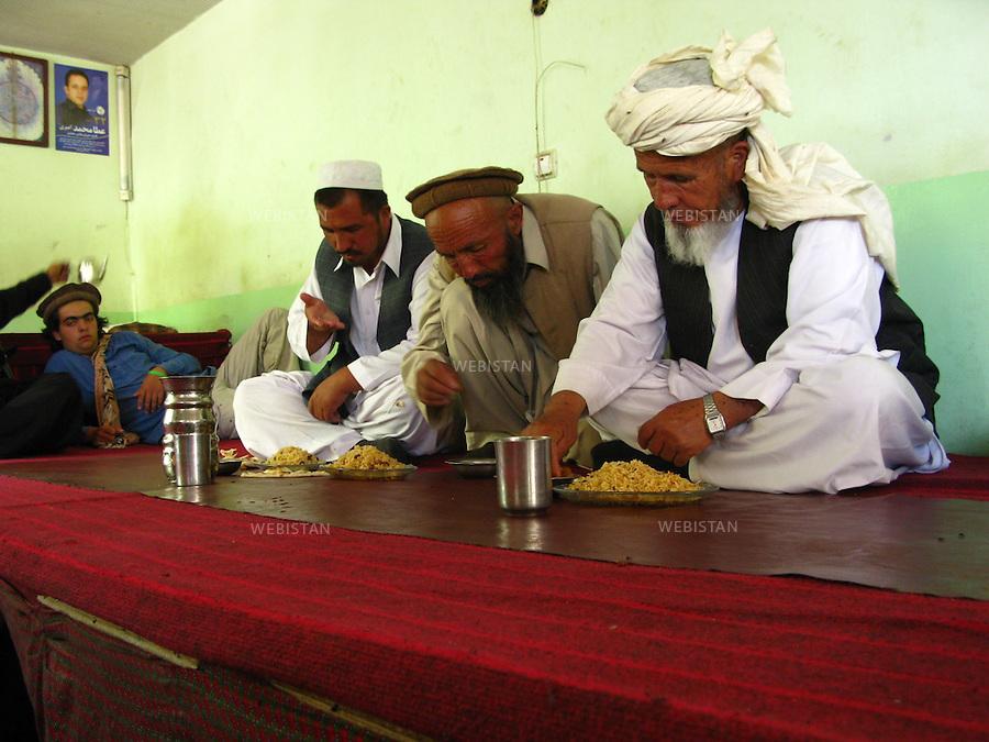 AFGHANISTAN - BAZARAK - 13 aout 2009 : Maison de the (Chai Khana). Delazad Deghati et trois hommes atables. ..AFGHANISTAN - BAZARAK  - August 13th, 2009 : Tea house (Chai Khana). Delazad Deghati and three men eating.