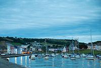 Pleasure boats - powerboats and yachts in harbour - seaside housing at sundown / dusk in Aberaeron, Pembrokeshire, Wales, UK