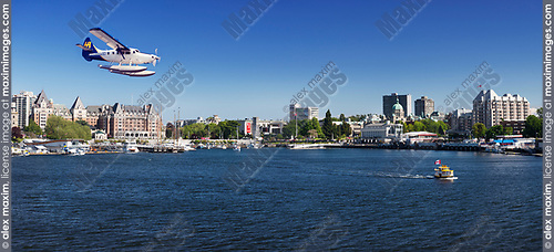 Harbour Air seaplane landing on water and H2O taxi sea taxi boat in front of a panoramic scenery of Victoria BC harbour front skyline. Victoria, Vancouver Island, British Columbia, Canada 2017.