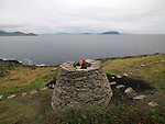 21-9-2012: Noelle Campbell Sharp, founder of the Cill Rialaigh Art project, (the restoration of a famine village in 1991) peers out from the 'Cairn' made and unveiled in her honour in Ballinskelligs, County Kerry on Friday. The villahe has housed thousands of artists from all over the world during the past 21 years. The Cairn, a pile of rock on a sacred space overlooks The Hogs Head and Scarriff Islands and will be used by artists for inspiration in their work.<br /> Picture by Don MacMonagle