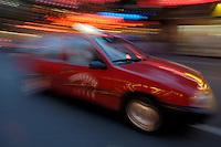 Taxi passes by the Wangfujing markets with great speed at night in Beijing, China.