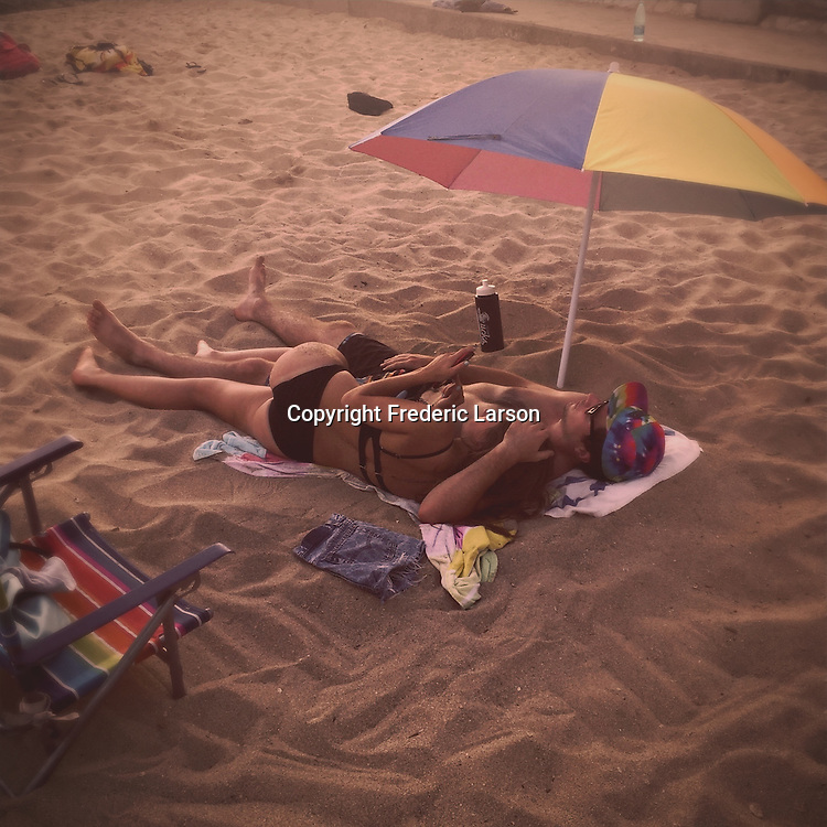 A couple enjoys a restful spot on Waikiki Beach, Hawaii.
