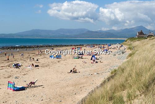 Llandanwg beach with summer holidaymakers.  Gwynedd North Wales UK. Snowdonia National Park in distance.