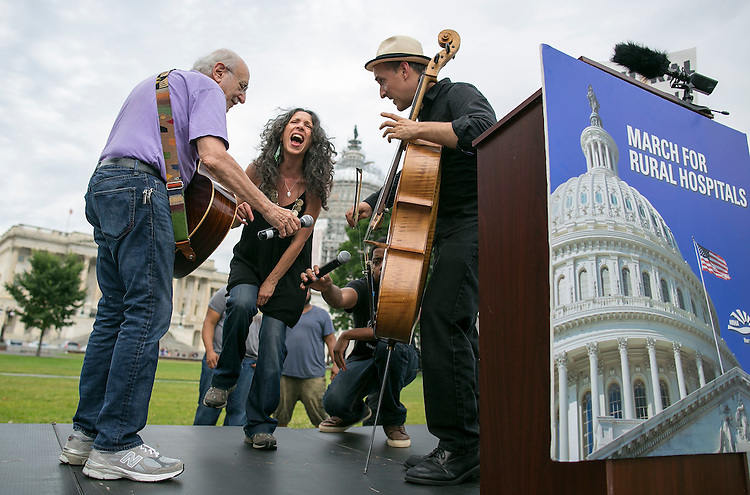 UNITED STATES - JUNE 15 - From left, Peter Yarrow, Bethany Yarrow, and Rufus Cappadocia, all from New York, sing and dance during a rally by the National Rural Health Association on the Southeast lawn of the U.S. Capitol on Monday, June 15, 2015. Around 20 members of the group marched 283 miles from Belhaven, N.C. to the Capitol, symbolizing one mile for each rural hospital that is at risk of closing. (Photo By Al Drago/CQ Roll Call)
