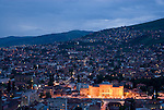 View of Sarajevo at dusk. During the war, the illuminated library building was repeatedly targeted in an effort to destroy the books inside.