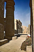 Egyptian man sitting next to Hypostyle Hall at The Ramessuem on the West Bank at Luxor, Egypt. Built by Ramesses II.
