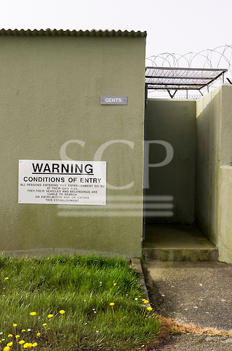 Culdrose, Cornwall, England. Gents toilet with warning sign: conditions of entry...