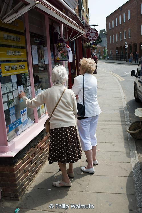Two elderly women look  at notices in a newsagent's shop window in Eton, Berkshire.