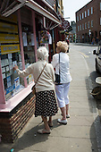 Two elderly women look  at notices in a newsagent's shop window in Eton, Berkshire.