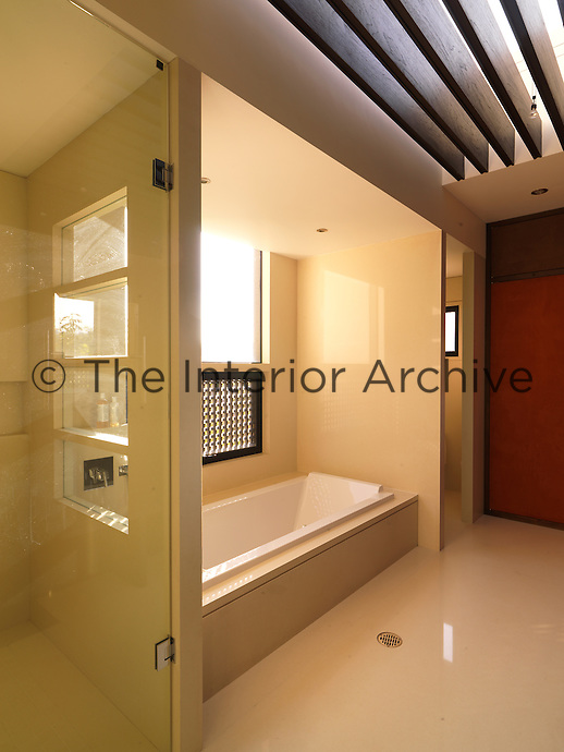 The bath is tucked in between the toilet cubicle and the walk-in shower in this spacious bathroom