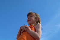 Young girl on beach with towel looking out to sea.