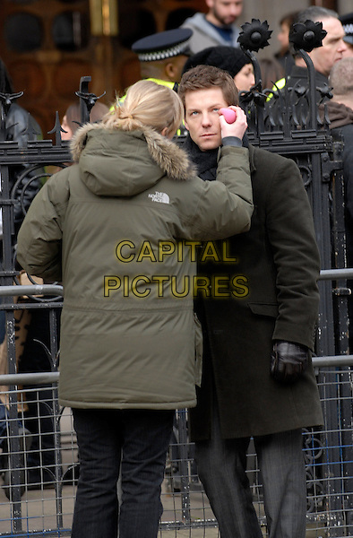 """JAMIE BAMBER .Filming on the set of """"Law & Order: UK"""" (Season 1, Episode 1), Royal Courts of Justice, London, England..February 15th, 2009.full length brown trenchcoat brown eye drops make-up 3/4 .CAP/IA.©Ian Allis/Capital Pictures."""