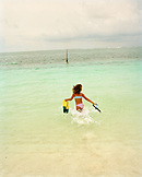 MEXICO, Maya Riviera, girl with snorkel and mask running into the Caribbean Sea