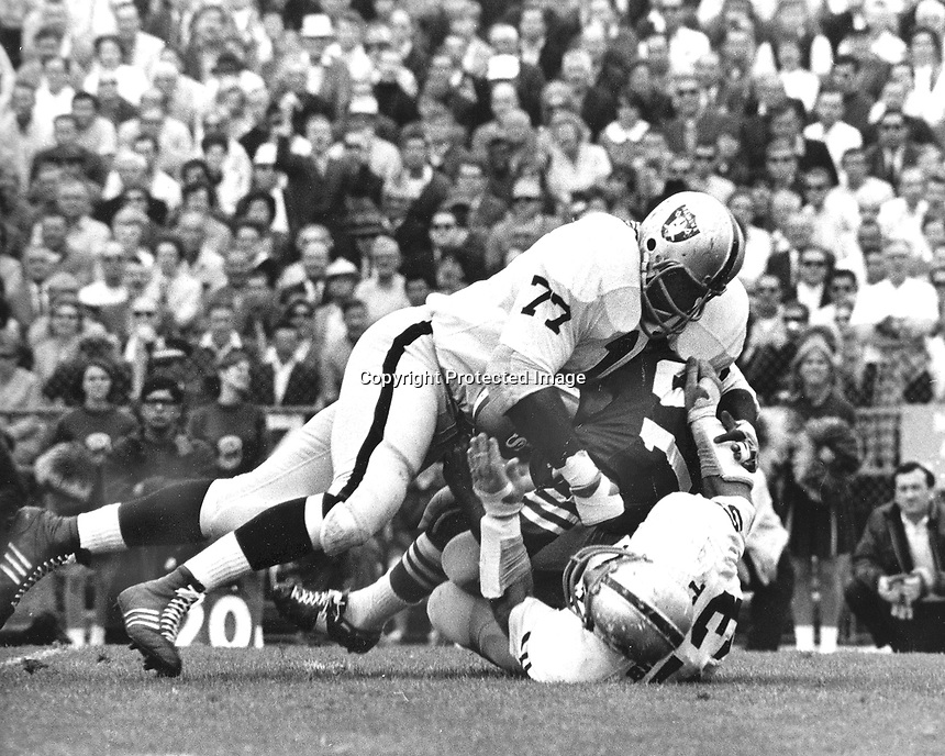 Oakland Raiders Ike Lassiter #77 and Dan Birdwell.sack 49er quarterback George Mira..(1968 photo/Ron Riesterer)