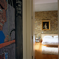 A glimpse into the master bedroom with a back wall of exposed brick