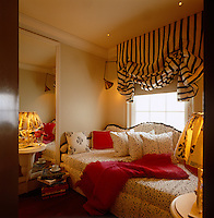A day bed has been covered in a polka dot fabric and placed in front of a sash window dressed with a striped Roman blind