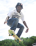 """The Gazette Tyrone Tolliver, 16 of Bowie soars through the air as he practices for the """"Skate Not Hate"""" skatebording competition on Sunday morning at Allen Pond Park in Bowie."""