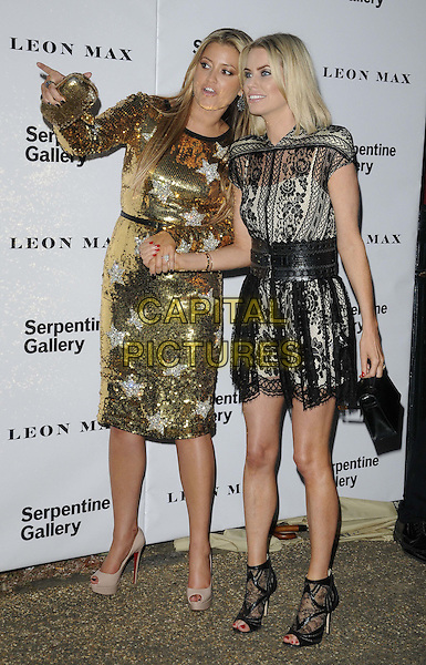 Holly Valance & Caroline Stanbury.Serpentine Galley Summer Party, Kensington Palace Gardens, London, England..26th June 2012.full length black belt silver gold stars print sequins sequined dress holding hands black lace clutch bag arm finger pointing .CAP/CAN.©Can Nguyen/Capital Pictures.