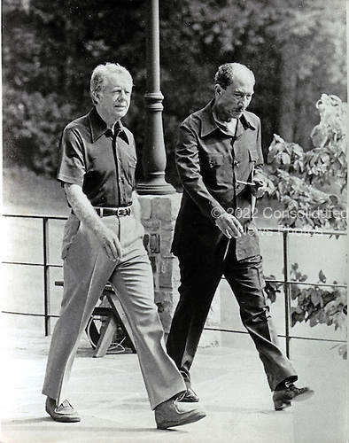 United States President Jimmy Carter, left and President Anwar Sadat of Egypt, right, walk behind Aspen Lodge at Camp David, near Thurmont, Maryland prior to their meeting on Tuesday, September 12, 1978..Credit: White House via CNP
