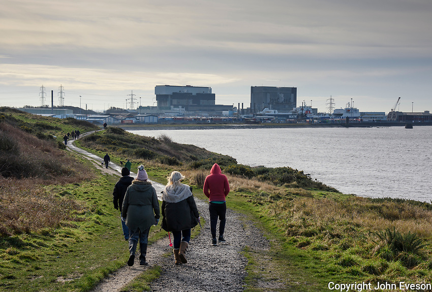 Walkers walking towards Heysham Nuclear power station, Lower Heysham, Lancaster, Lancashire.