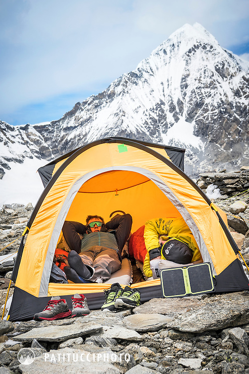 Ueli Steck and David Göttler inside their tent at Shishapangma's advance basecamp, using a solar panel to charge batteries, relaxing and waiting for a weather window to climb, during the climbing expedition to the 8000 meter peak Shishapangma, Tibet