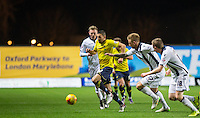 Liam Sercombe of Oxford United heads forward under pressure from Millwall players during the Johnstone's Paint Trophy Southern Final 2nd Leg match between Oxford United and Millwall at the Kassam Stadium, Oxford, England on 2 February 2016. Photo by Andy Rowland / PRiME Media Images.