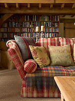 A sofa covered in a red-and-white plaid is piled with pretty floral scatter cushions in the double-height living area