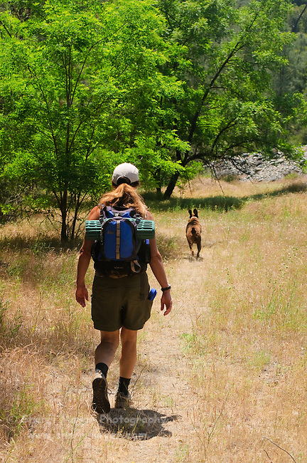 Woman hiking with her dog along the North Fork of the American River, Weimar, California.