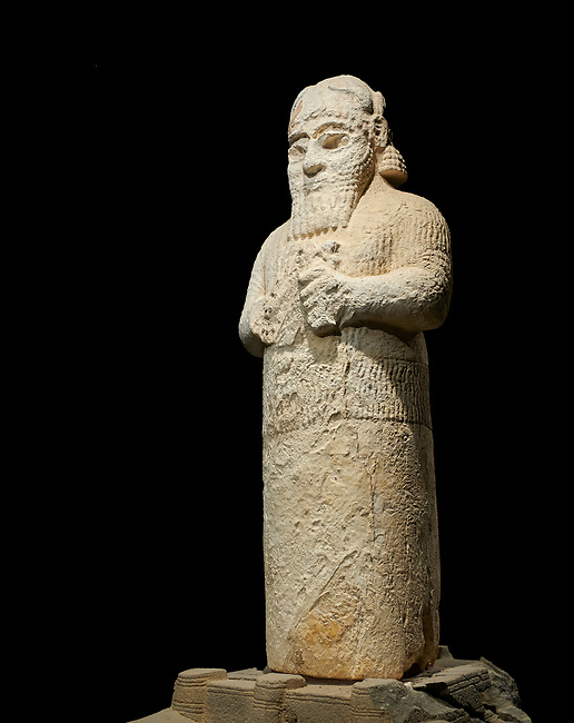 Hittite monumental statue probably of Tarhunda, the Storm God, standing on a cart being pulled by two bulls. Adana Archaeology Museum, Turkey. Against a black background