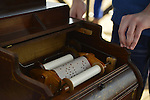 Organ grinder Ian Fraser plays a 1881 Celestina Organette, made by the Mechanical Orguinette Company of New York, at the Fourth Annual History Day at Deno's Wonder Wheel Amusement Park and The Coney Island History Project. The music roll, with holes where notes play, is shown in the closeup.