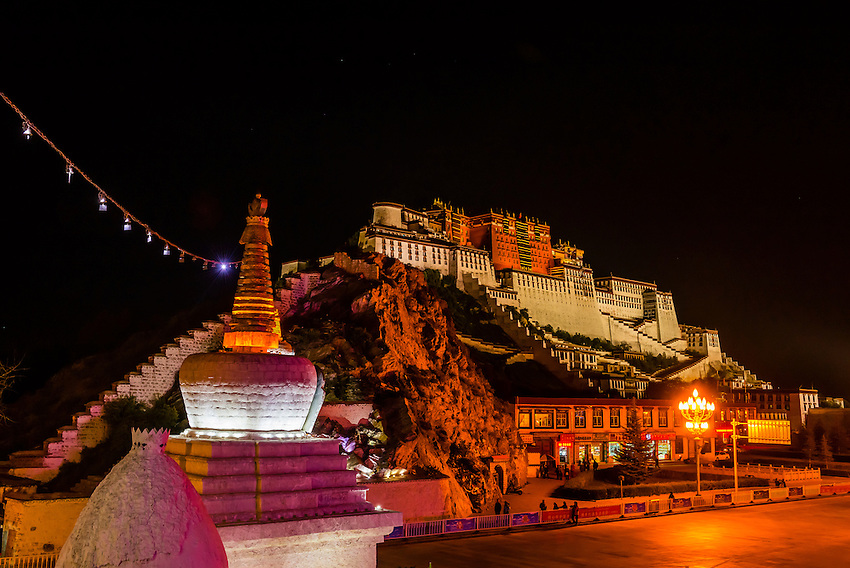 The Potala Palace with stupas in the foreground illuminated at night, Lhasa, Tibet (Xizang), China.