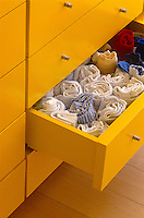 In a bedroom of a house designed by Richard Rogers neat rows of underwear and socks are arranged in a chest of drawers lacquered bright yellow
