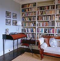 A contemporary roll-top desk sits in a corner of the library