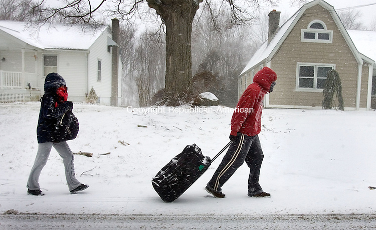 WOLCOTT, CT. 08 February 2013-020813SV11-With luggage in tow, from left, Tina Mason and Michael Spooner both of Wolcott make the trek up Woodtick Road on the way to a relatives house to sit out the storm in Wolcott Friday. .Steven Valenti Republican-American