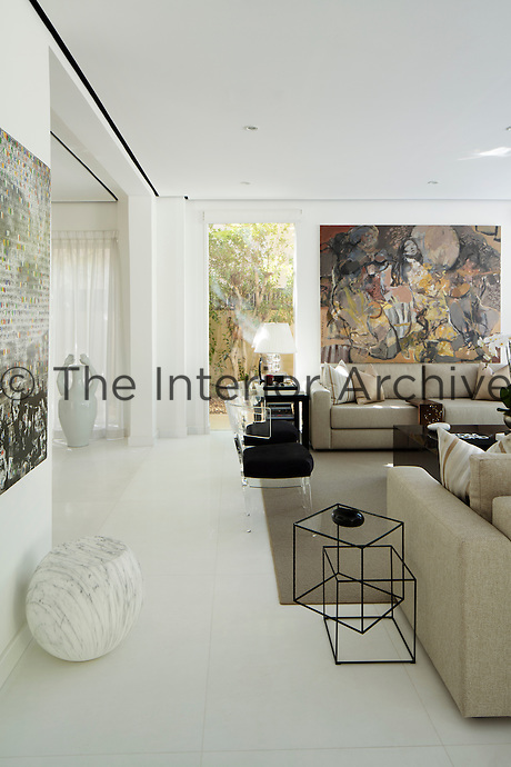 The spacious living room has white walls and flooring. Two sofas upholstered in a neutral fabric face each other over a coffee table. The walls are hung with large artworks.