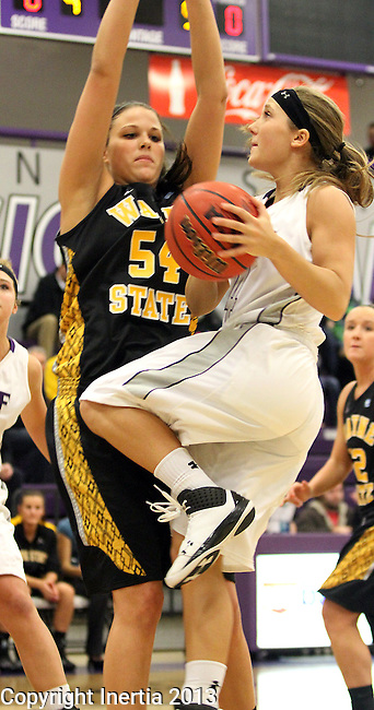 SIOUX FALLS, SD - DECEMBER 6:  Marie Malloy #4 from the University of Sioux Falls drives into the defense of Shantel Lehmann #54 from Wayne State in the first half of their game Friday night at the Stewart Center. (Photo by Dave Eggen/Inertia)