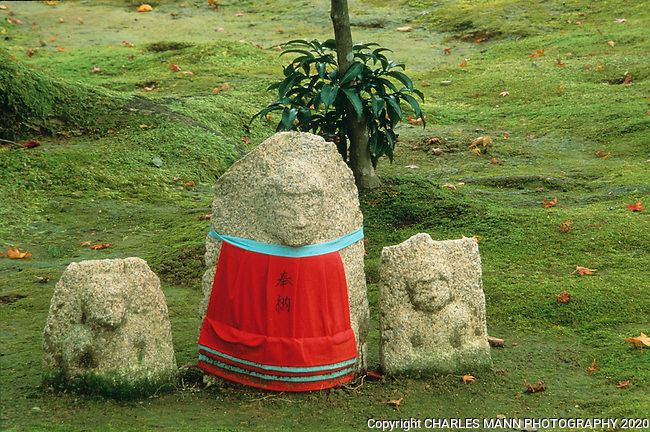 Simple stone figures set on a mossy floor with a Buddha like image seem to blend the Buddhist and Shinto sensibilities.