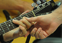 NWA Democrat-Gazette/FLIP PUTTHOFF<br /> FINGERS AT WORK<br /> John Yount's fingers get help from the hand of guitar instructor Mike Haley during guitar lessons Tuesday August 18 2015 at the Adult Wellness Center in Rogers. About a dozen students are enrolled in guitar lessons at the center. A picking circle is held at 1 p.m. each Tuesday for any guitar players who wish to play and sing.