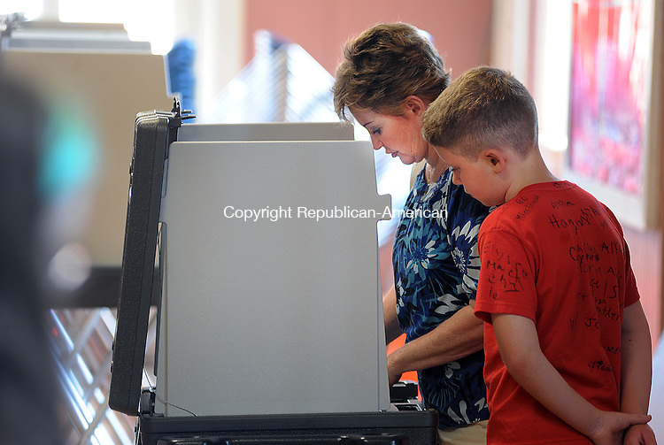 THOMASTON, CT-20 JUNE 2012--062012JS09-Brian Perkins Jr., 10, of Thomaston, looks on as his grandmother Betty Letourneau cast her vote during the budget referendum Wednesday at Thomaston Town Hall. . Jim Shannon Republican-American