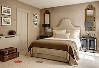 A guest bedroom furnished in neutral and taupe tones. Two metal lamps stand on bedside cabinets either side of a double bed with an upholstered headboard.