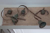 A band of rusting bells has been mounted on a board above the square arch that divides the kitchen and dining room