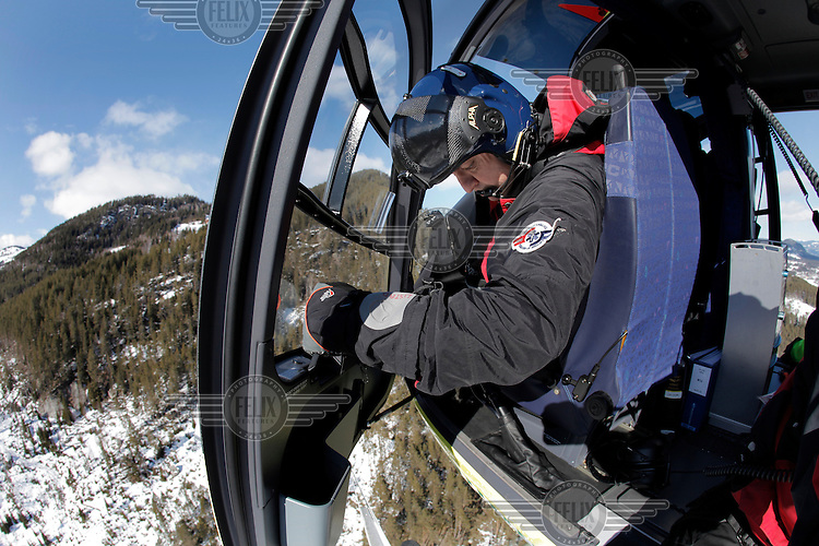 Crew from Norwegian Air Ambulance practice rescue skills at Camp Torpomoen, a training facility..Pilot Ole Anders Listad looking out of  a helicopter during pick up training.