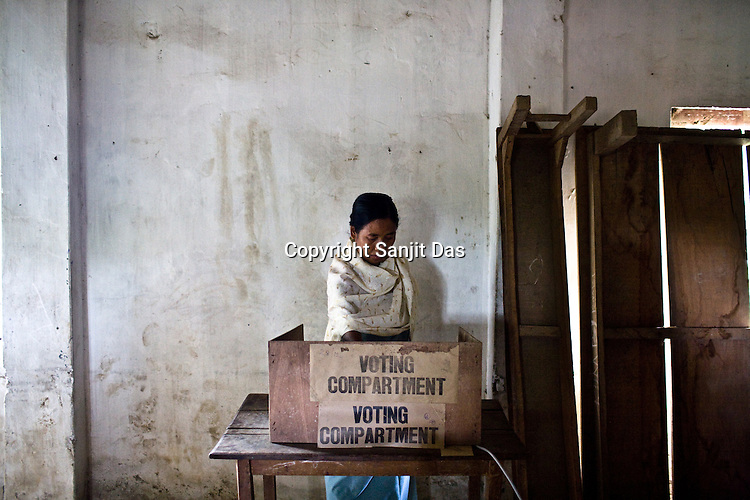 A local villager is seen casting his vote in a polling booth amidst high security in village  Kumbi, Manipur, India. About 62 per cent of 8,02,000 voters exercised their franchise in an incident-free secondphase of Lok Sabha elections for the prestigious Inner Manipur parliamentary constituency on April 22nd 2009.