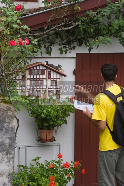 Europe/France/Aquitaine/64/Pyrénées-Atlantiques/Ascain: Facteur déposant le courrier dans une boite aux lettres en forme de  maison basque